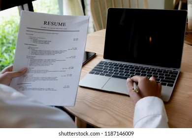 Business man review his resume application on desk, laptop computer, job seeker