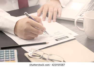 Business man review his resume on his desk, laptop computer, calculator, warm tone.