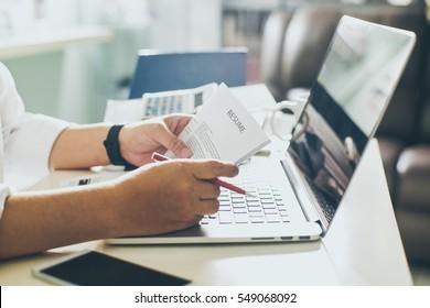 Człowiek biznesu przeglądu jego CV na biurku, laptop, kalkulator i filiżanka kawy, Seleted fokus.