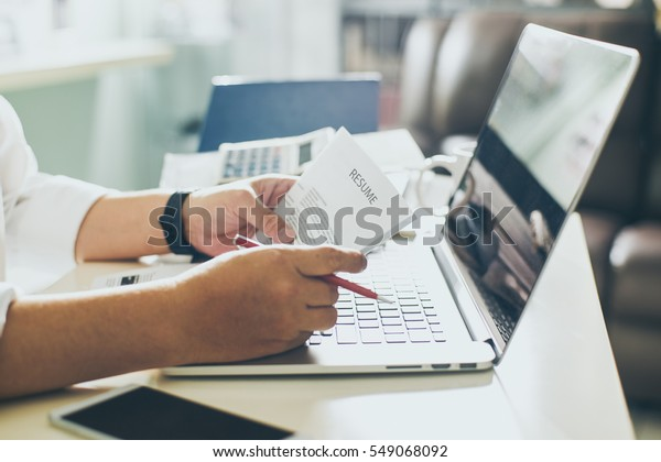 Business man review his resume on his desk, laptop computer, calculator and cup of coffee,Seleted focus.