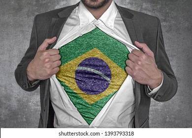 Business man rips open his shirt to show t-shirt with flag of Brasil