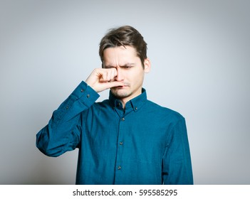 Business man rubs tired eyes with hands, isolated on gray background