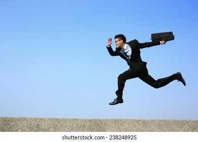 business man running with blue sky background, full length, asian male