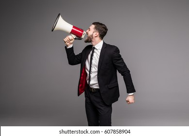 Business man screaming with a megaphone on grey background