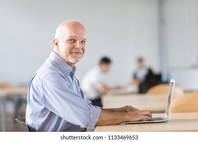 Business man seated and looking at camera while working on on laptop computer.