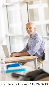 Business man seated and looking at camera while working on laptop computer.