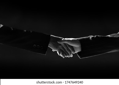 Business man shakes hands with Suit woman as western manner to say hello greeting, corona virus or covid-19 disrupt this meeting style, new normal Business Lifestyle concept, Dark low exposure