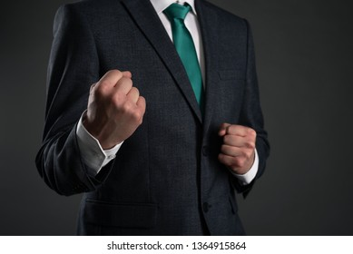 Business man is shaking a fists on a gray background. Business acumen or business protection. Leadership. Defending point of view abstact background.