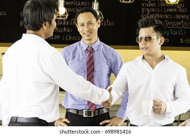 Business man shaking hands with customer after after successful deal. Business people shaking hand afer finishing up a meeting.