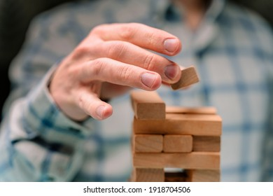 Business man in a shirt builds a tower of wooden blocks as a symbol of development and planning in business, a strategy for success