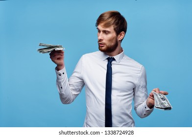 A business man in a shirt and tie holding a bundle of money in his hands on a blue background