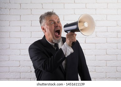 Business man shouts in loudspeaker, a man yells into a mouthpiece