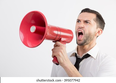 Business man shouts in a red loudspeaker against white background