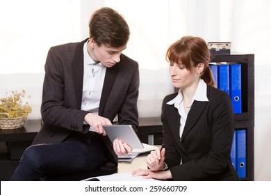 Business man show something on the tablet and working together with colleagues.