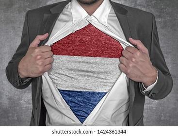 Business man show t-shirt flag of Netherlands rips open his shirt