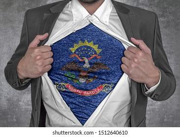 Business man show t-shirt flag of USA state North Dakota rips open his shirt