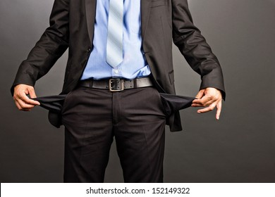 Business man showing his empty pockets  on gray background