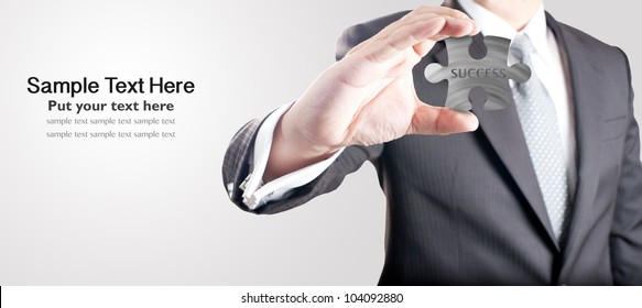 """Business man showing metal jigsaw puzzle piece with """"SUCCESS"""" wording. Concept for business strength and success."""