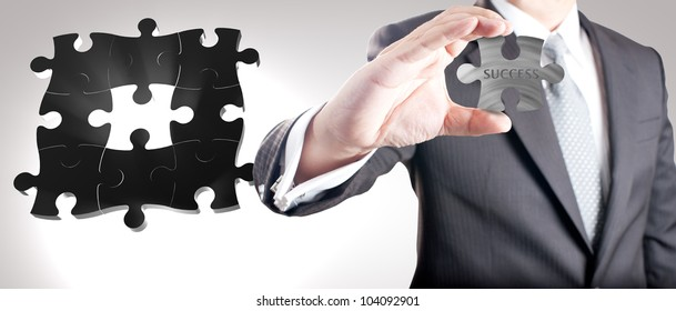 """Business man showing missing metal jigsaw puzzle piece with """"SUCCESS"""" wording. Concept for business strength and success."""