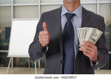 Business Man showing money with thumb up with empty flip chart, white board. Success, investment, financial growth, profit, dividends concept. Copy space image or text.