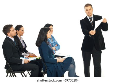 Business man showing paperwork at seminar and the team of people looking attentive to his presentation