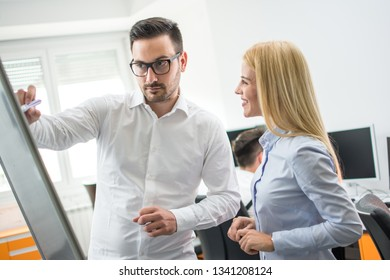 Business man showing scheme on flipboard to his female colleague at office