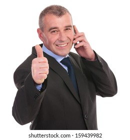 business man showing the thumb up gesture while on phone, with a smile on his face. on a white background