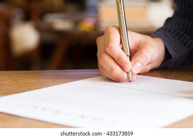 business man signing contract document on office desk