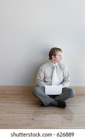 business man sits and looks out while typing on his laptop on a wood floor