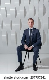 Business man sits on chair against background of abstract modern urban interior