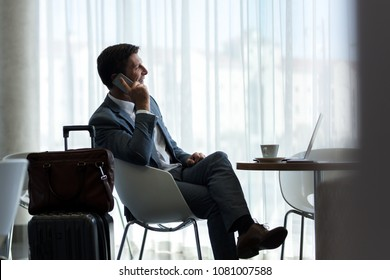Business man sitting at airport lounge and talking on mobile phone. Male business traveler sitting at airport waiting area with suitcase waiting for the flight.