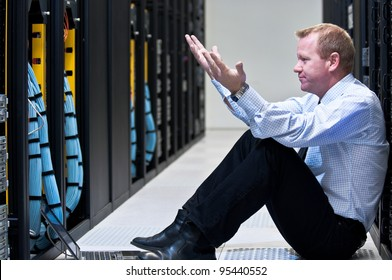 Business man sitting in a data center looking frustrated with the current system. He is looking for a better IT solution