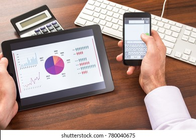 Business man sitting at desk looking at tablet and texting on phone.