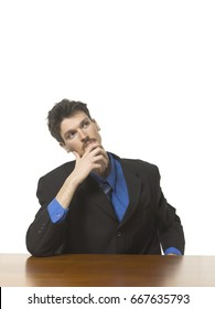 Business man sitting at a desk thinking