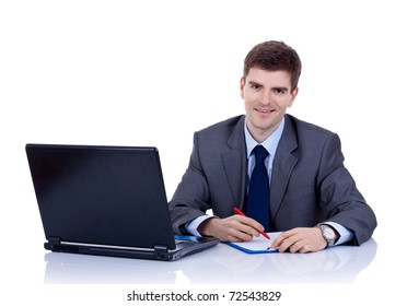 Business man sitting at desk, writing notes on paper, smiling. Isolated on white background
