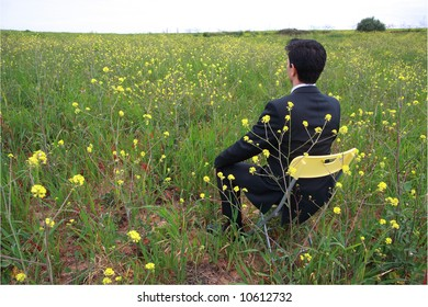 A business man sitting in a field with flowers
