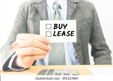 business man sitting at office desk word Buy or Lease on white card