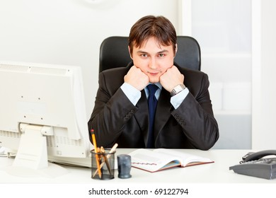 Business man sitting at office desk and keep head on hands