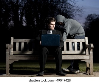 Business man sitting on a park bench, using his laptop, whilst a hooded stranger attempts pickpocket him.