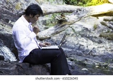 Business man sitting on the rock with his laptop and thinking about problems at waterfalls.