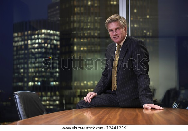Business man sitting on table in boardroom looking at camera