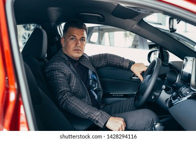 Business man sitting in red bussines  car