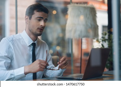 business man sitting at a table in hand glasses cafe