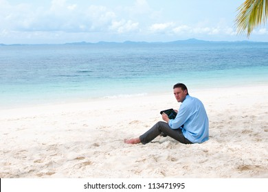 Business man sitting and working on the beach with tablet computer
