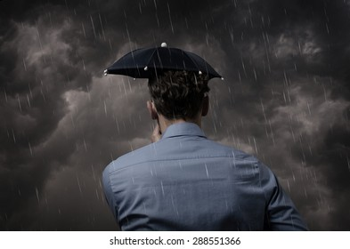 Business man with small umbrella in front of a heavy storm