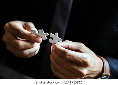 Business man solutions, success and strategy concept. Businessman hand connecting jigsaw puzzle
