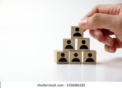 Business man stacking wooden team blocks at table for team management concept or human resource planning