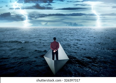 Business man standing alone on paper boat, looking at the horizon