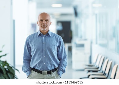 Business man standing and facing the camera with hands in pocket.