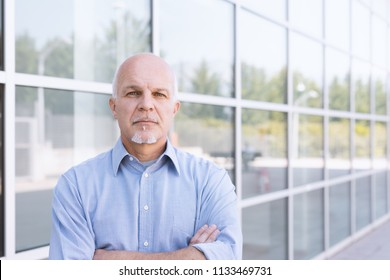 Business man standing and facing the camera expressionless with backdrop of windows.